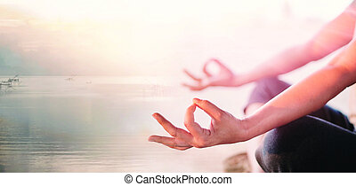 Young woman yoga practicing and meditating by the sea in summer background