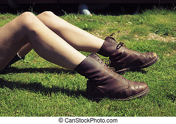 Young woman's legs and feet on the grass