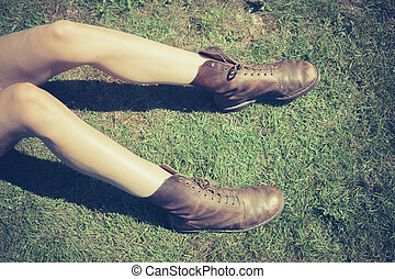 Young woman's legs on the grass