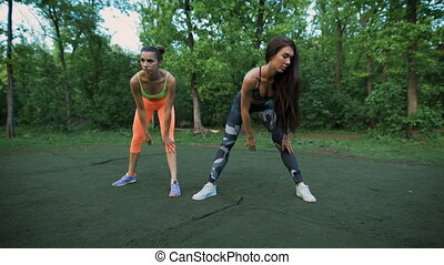 Young womans stretches before doing sports