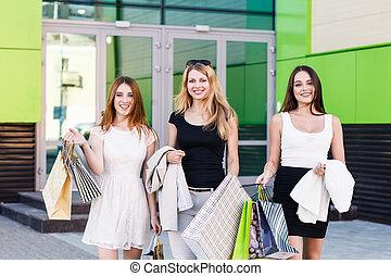 Young women after shopping - Three young women walking on a...