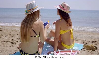 Young women applying sunscreen to protect their skins as...