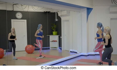 Young women are warming up while standing in sports club....
