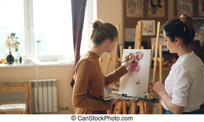Young women art teacher and student are having lesson at...