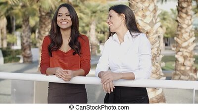 Young women chatting in a tropical urban park