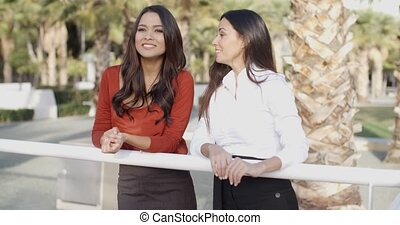 Young women chatting in a tropical urban park - Two...