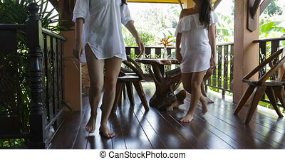Young Women Coming In Living Room From Terrace Talking Sit On Couch, Group Of Female Friends Communication