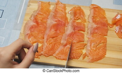 Young Women Cuts Salmon Meat into Small Pieces on Cutting Board at Home Kitchen