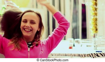 Young women dance and drink alcohol in the kitchen