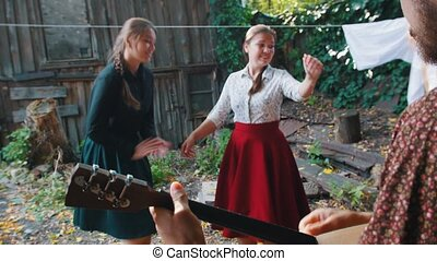 Young women dancing and having fun in the village -...