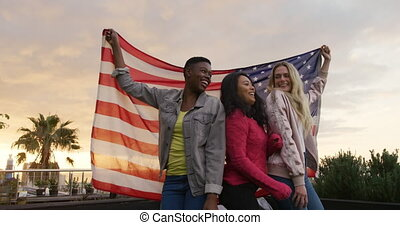 Young women dancing and holing the American flag on a ...