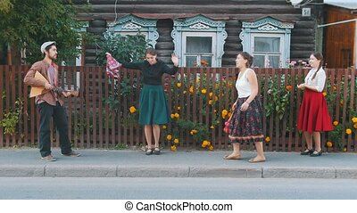 Young women dancing folk dances on the street in the village...