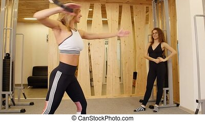 Young women doing fitness. A woman doing strength exercises on her hands in the gym. Another woman watching her
