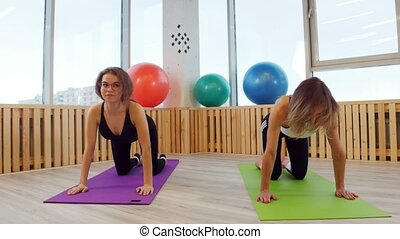 Young women doing fitness in the studio. Bending the back....