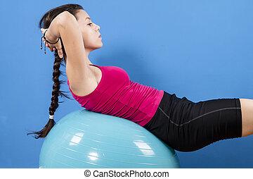 Young women doing pushups on fitness ball.