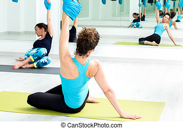 Young women doing stretching exercises in gym.