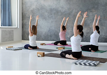 young women doing yoga exercise, lying in Hero pose, Virasana