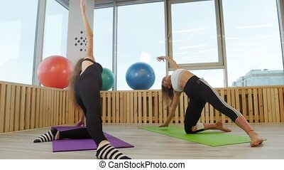 Young women doing yoga in the gym. Doing breathing exercises