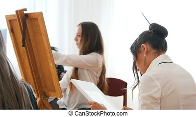Young women drawing on a canvas, sitting behind an easel