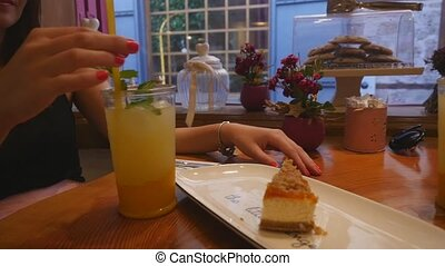 Young women drinking lemonade and eating cakes at the cafe