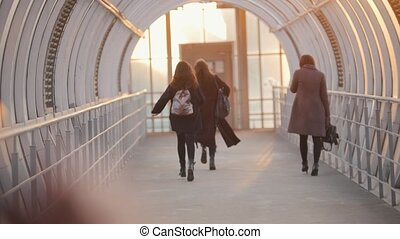 Young women fast run across the overhead passage, back view