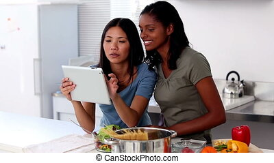 Young women following online recipe on a tablet pc before...