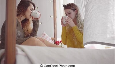 Young women friends chat and drink tea in the bedroom, sitting on the bed