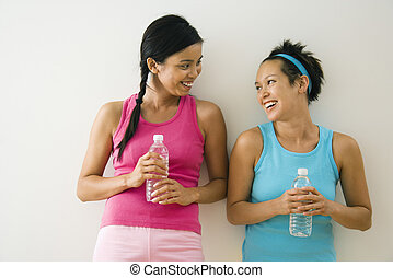 Young women friends - Two young women standing in workout ...