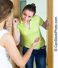 Young women having conflict at the door