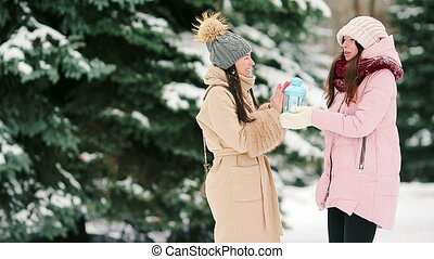 Young women holding candlelight outdoors on beautiful winter snow day and having fun