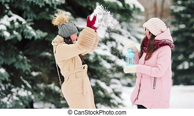 Young women holding candlelight outdoors on beautiful winter snow day and warm their hands