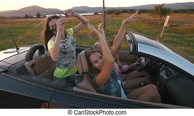 Young women in a convertible car - Attractive young women in...