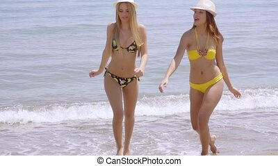 Young women in bikinis frolicking in the sea