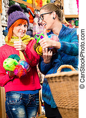 Young women in knitting fashion shop