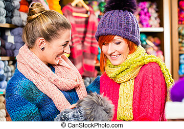 Young women in knitting shop shopping fashion