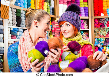 Young women in knitting shop - Young women buying colorful...