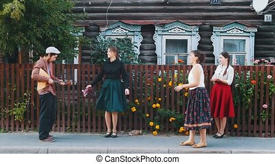 Young women in long skirts dancing folk dances on the street...