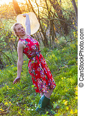 Young women in red dress on green grass.
