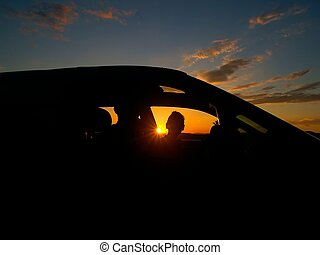 young women in the car against the sun-down