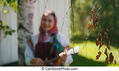Young women in traditional Russian clothes standing near a...