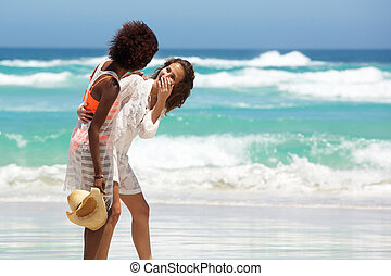 Young women laughing at the beach