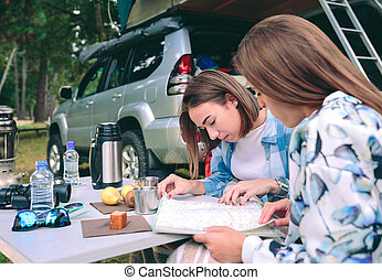 Young women looking road map with 4x4 on background