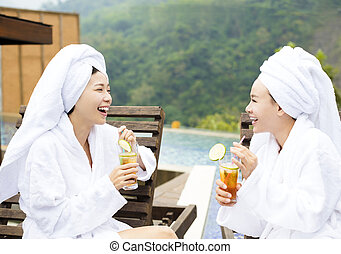 young Women relaxing and drinking tea in spa salon