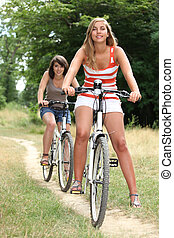 Young women riding bikes in the countryside