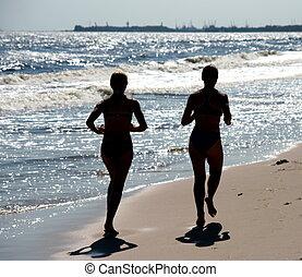 Young women running on a beach