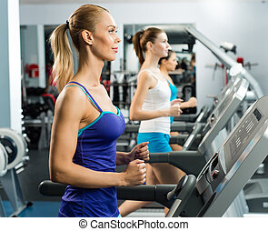 young women running on a treadmill