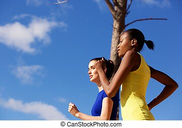 Young women running together outdoors