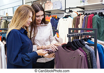 Young women shopping and looking at some clothing in a store...