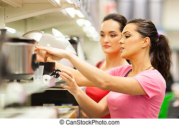 young women shopping for appliance in supermarket