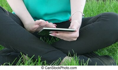 Young women sitting in grass with crossed legs and working tablet PC UHD